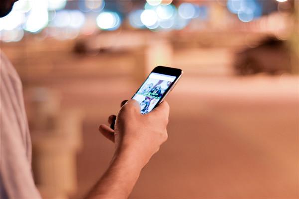 Ein User, der mit seinem Smartphone durch die SERPs scrollt